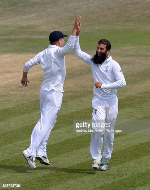 England's Moeen Ali celebrates with team mate Gary Ballance after taking the wicket of India's Mohammed Shami claiming his fifth wicket during day...