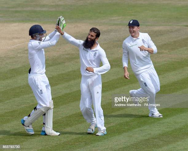 England's Moeen Ali celebrates with team mate Gary Ballance and Jos Buttler after taking the wicket of India's Mohammed Shami claiming his fifth...