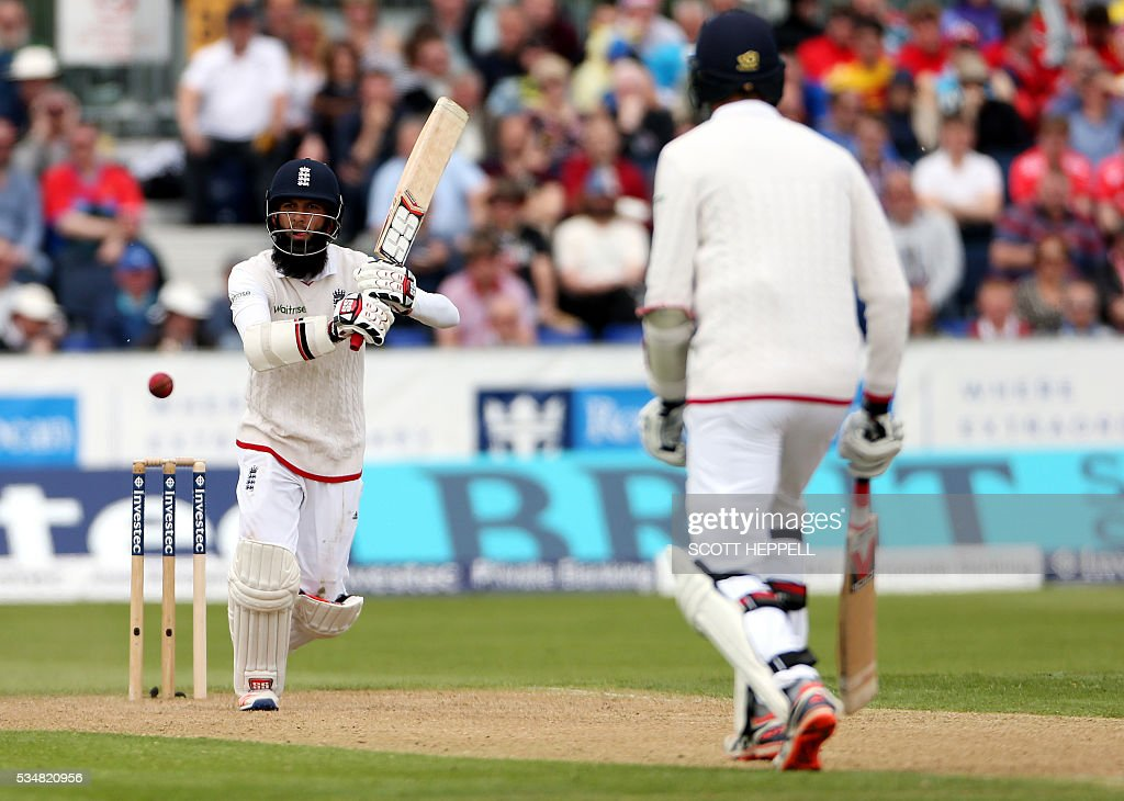 England's Moeen Ali (L) plays a shot on the second day of the second test cricket match between England and Sri Lanka at the Riverside in Chester Le Street, north east England on May 28, 2016. / AFP / SCOTT
