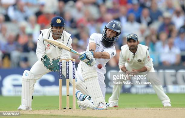 England's Moeen Ali plays and misses from the bowling of India's Ravichandran Ashwin watched by Mahendra Dhoni and Virat Kohli during the Fourth...