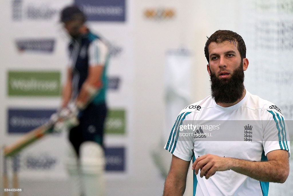 England's Moeen Ali (R) reacts during an indoor practise session ahead of the second cricket Test match between England and Sri Lanka in Chester-le-Street, north east England on May 26, 2016. England may come into the second Test against Sri Lanka in Durham on the back of a crushing win in the series opener, but according to Stuart Broad the hosts have still to hit top form. England are set to play Sri Lanka in a second test cricket match on May 27. / AFP / SCOTT