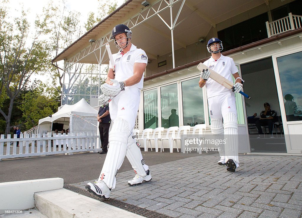 England's (L) Nick Compton and Steven Finn walk out to the field at the start of the days play during day four of the first international cricket test match between New Zealand and England played at the University Oval park in Dunedin on March 9, 2013. AFP PHOTO / Marty MELVILLE