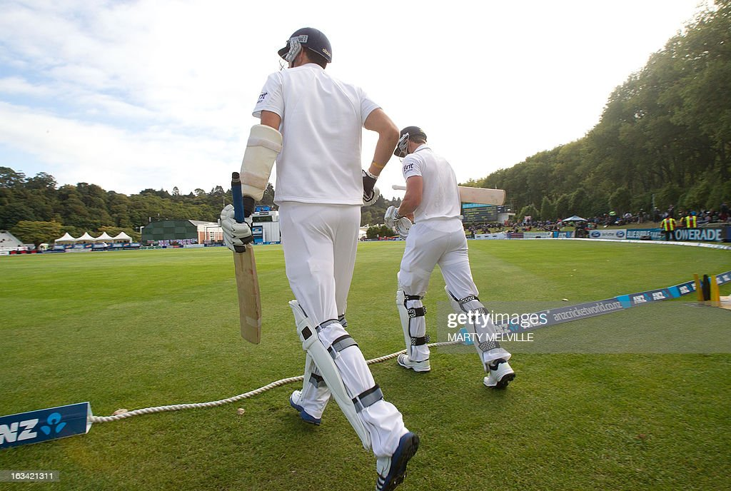 England's Nick Compton (L) and Steven Finn walk out to the field at the start of the days play during day four of the first international cricket test match between New Zealand and England played at the University Oval park in Dunedin on March 9, 2013. AFP PHOTO / Marty MELVILLE
