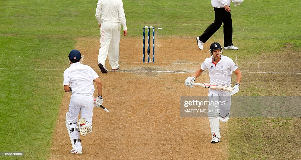 England's Nick Compton (R) makes a run with teammate captain Alastair Cook during day four of the first international cricket Test match between New Zealand and England played at the University Oval park in Dunedin on March 9, 2013. AFP PHOTO / Marty MELVILLE
