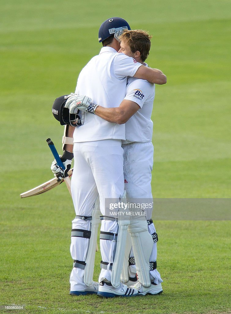 England's Nick Compton (R is hugged by teammate Steven Finn after he scored 100 runs during day four of the first international cricket Test match between New Zealand and England played at the University Oval park in Dunedin on March 9, 2013. AFP PHOTO / Marty MELVILLE