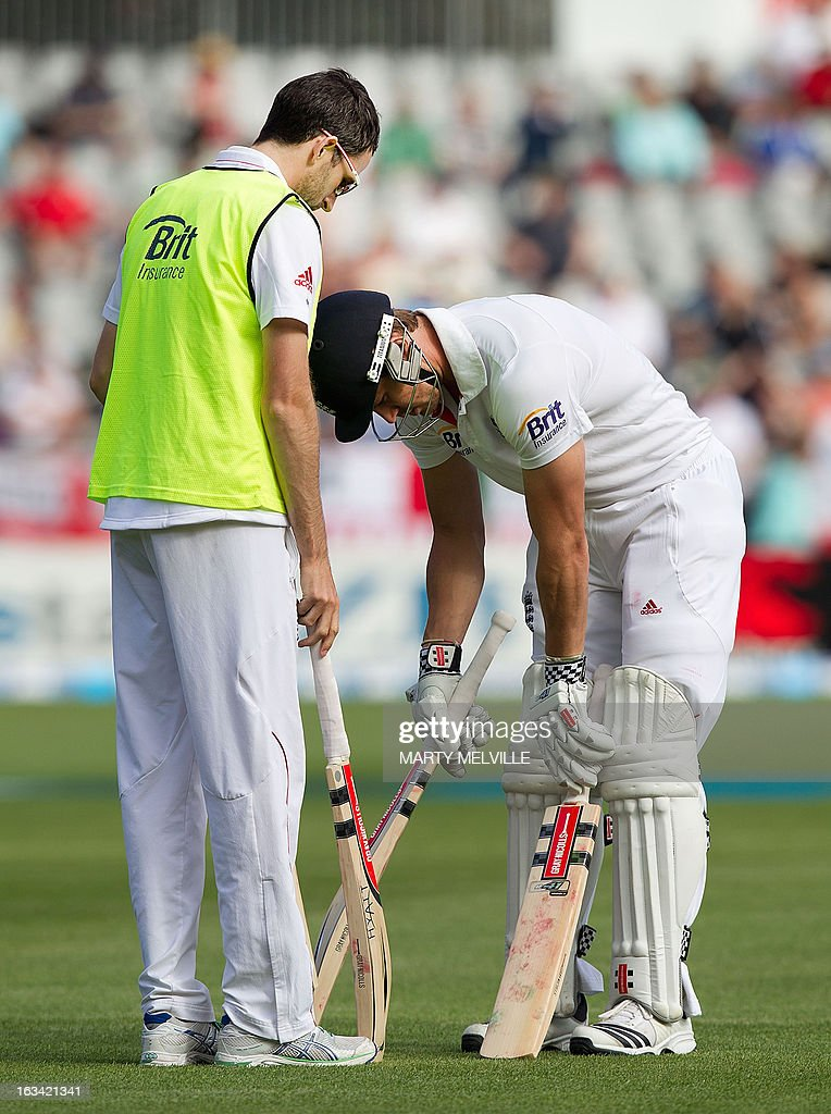 England's Nick Compton (R) selects a new bat with the help of a teammate during day four of the first international cricket test match between New Zealand and England played at the University Oval park in Dunedin on March 9, 2013. AFP PHOTO / Marty MELVILLE