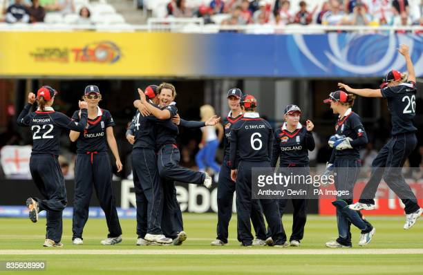 England's Nicky Shaw is congratulated by jubilant teammates after bowling out New Zealand's Nicola Browne during the Final of the Women's ICC World...