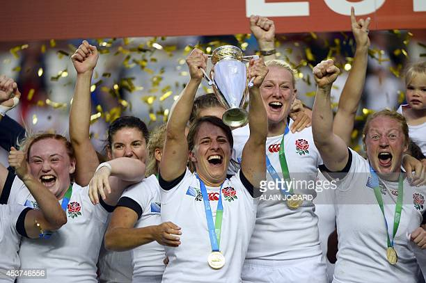 England's players celebrate with the trophy after winning the IRB Women's Rugby World Cup final match between England and Canada at the Jean Bouin...
