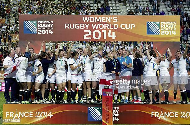 England's players celebrate with the trophy on the podium after winning the IRB Women's Rugby World Cup final match between England and Canada at the...