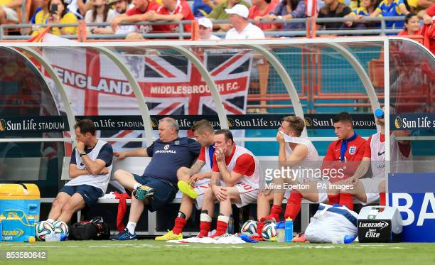 England's players including Wayne Rooney Luke Shaw and Ross Barkley watch the action from then bench