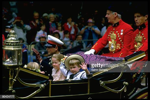 England's Prince Edward and Prince William in royal carriage waving while riding along fanlined route to church wedding of Prince Andrew Sarah...