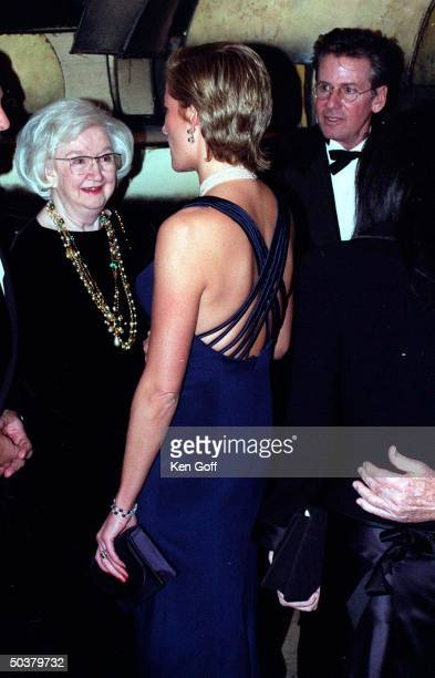 England's Princess Diana talking to unident showing off new sleek hairstyle jeweled choker navy blue strapped gown cut low in back at a charity gala...