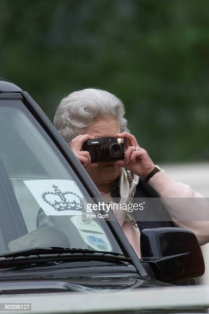 England's Queen Elizabeth II taking photography of her unseen husband Prince Philip competing at the Royal Windsor Horse Show carriage driving...