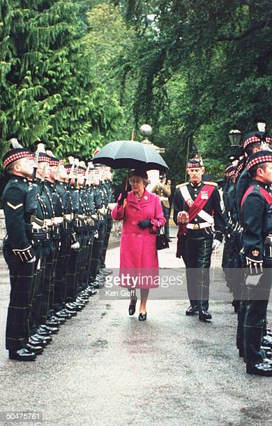 England's Queen Elizabeth II w unident commanding officer of Scottish Royal Guards regiment as she holds an umbrella during her inspection of the...