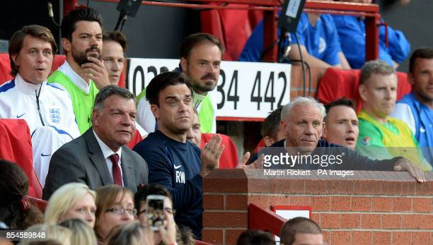 England's Robbie Williams watches the game from the bench with manager Sam Allardyce during the Soccer aid charity match at Old Trafford Manchester