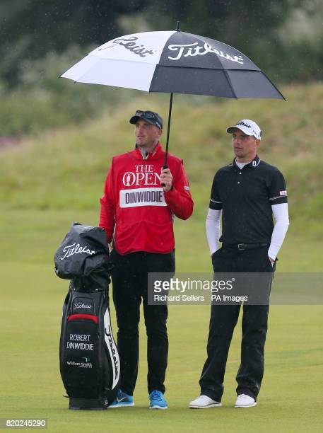 England's Robert Dinwiddie and caddie shelter from the rain during day two of The Open Championship 2017 at Royal Birkdale Golf Club Southport