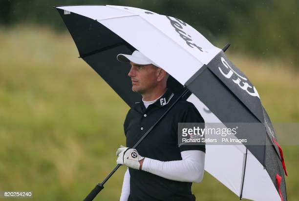 England's Robert Dinwiddie shelters under an umbrella during day two of The Open Championship 2017 at Royal Birkdale Golf Club Southport