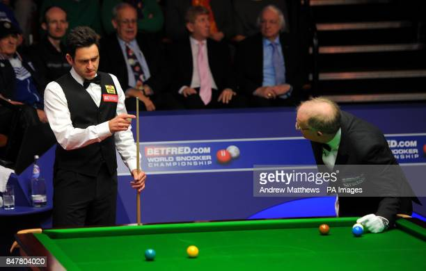 England's Ronnie O'Sullivan advises referee Leo Scullion on where to replace the white ball after fouling during his second round match against...