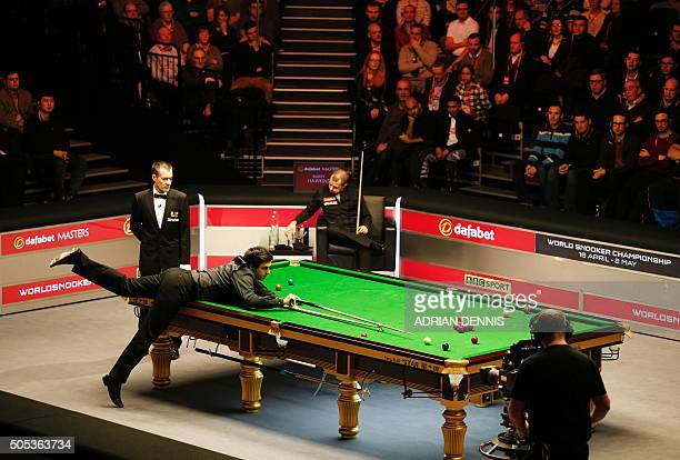 England's Ronnie O'Sullivan plays a shot during the Masters Snooker final against England's Barry Hawkins at Alexandra Palace in north London on...