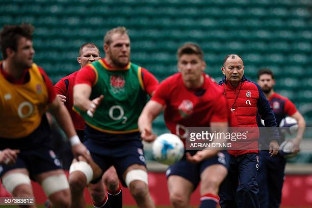 England's rugby union head coach Eddie Jones and captain Dylan Hartley look on as Owen Farrell passes the ball during a public training session at...