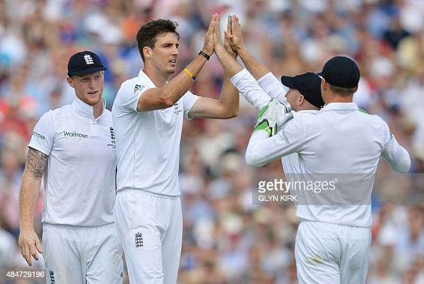 England's Steven Finn celebrates with teammates after taking the wicket of Australia's Mitchell Marsh on the second day of the fifth Ashes cricket...
