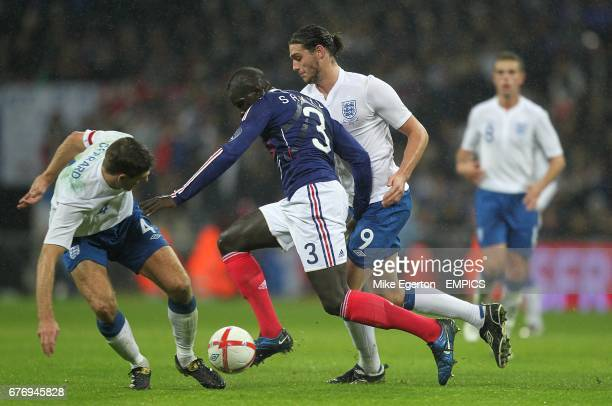 England's Steven Gerrard and Andrew Carroll battle for the ball with France's Mamadou Sakho