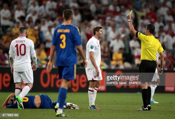 England's Steven Gerrard is shown a yellow card by referee Viktor Kassai