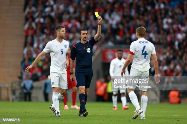 England's Steven Gerrard is shown the yellow card by referee Viktor Kassai