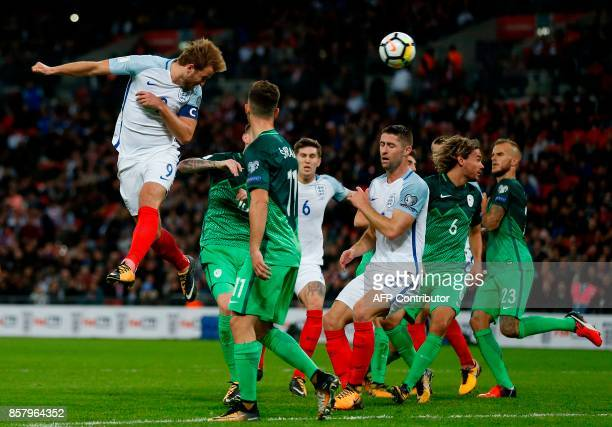 England's striker Harry Kane leaps to head the ball into the net but the goal is disallowed and Slovenia are awarded a free kick during the FIFA...