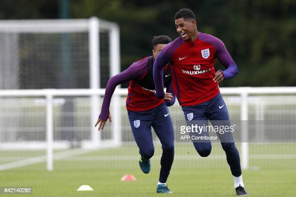 England's striker Marcus Rashford sprints away from England's midfielder Jesse Lingard during an England team training session at Tottenham Hotspur's...