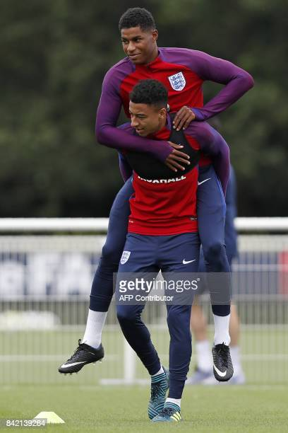 England's striker Marcus Rashford takes a ride on the back of England's midfielder Jesse Lingard during an England team training session at Tottenham...