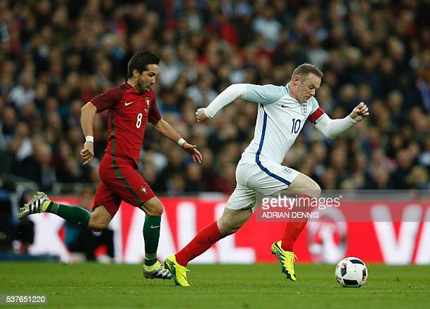 England's striker Wayne Rooney runs past Portugal's midfielder Joao Moutinho during the friendly football match between England and Portugal at...