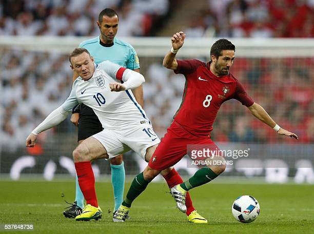 England's striker Wayne Rooney tackles Portugal's midfielder Joao Moutinho during the friendly football match between England and Portugal at Wembley...