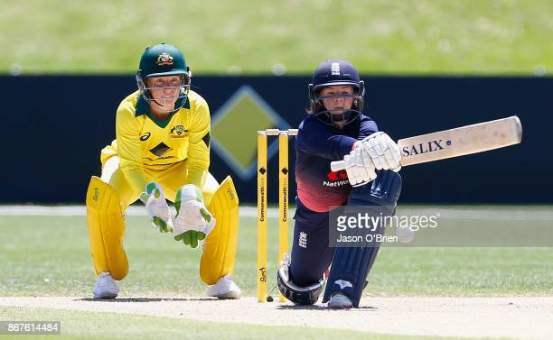 England's Tammy Beaumont plays a reverse sweep as Australia's Alyssa Healy looks on during the Women's International One Day match between Australia...