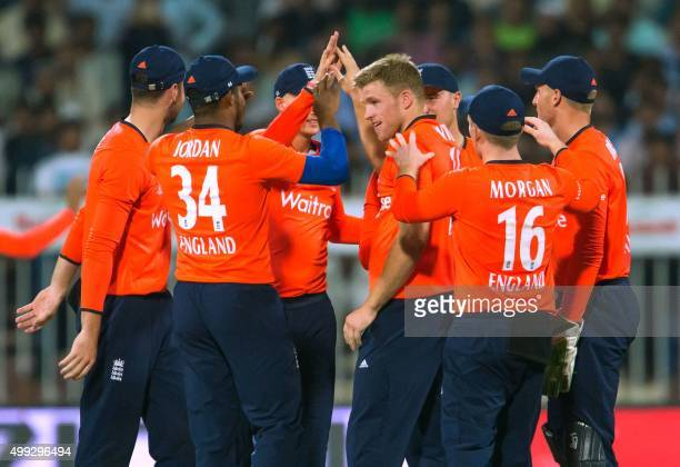England's team players celebrate the dismissal of Rifatullah Mohmand during third T20 cricket match between Pakistan and England at the Sharjah...