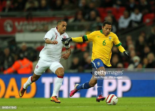 England's Theo Walcott amd Brazil's Adriano battle for the ball