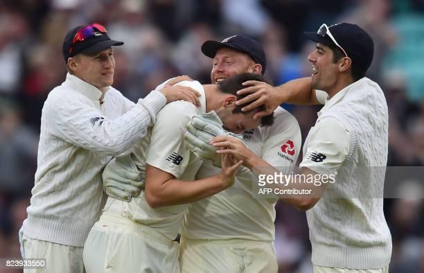 England's Toby RolandJones celebrates the wicket of South Africa's Hashim Amla for 6 runs with England's captain Joe Root and England's Stuart Broad...
