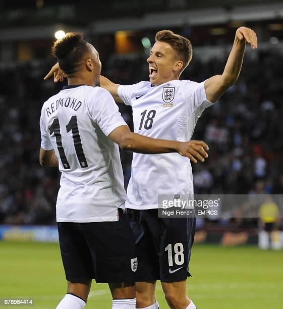 England's Tom Carroll celebrates with Nathan Redmond after scoring his sides sixth goal against Scotland