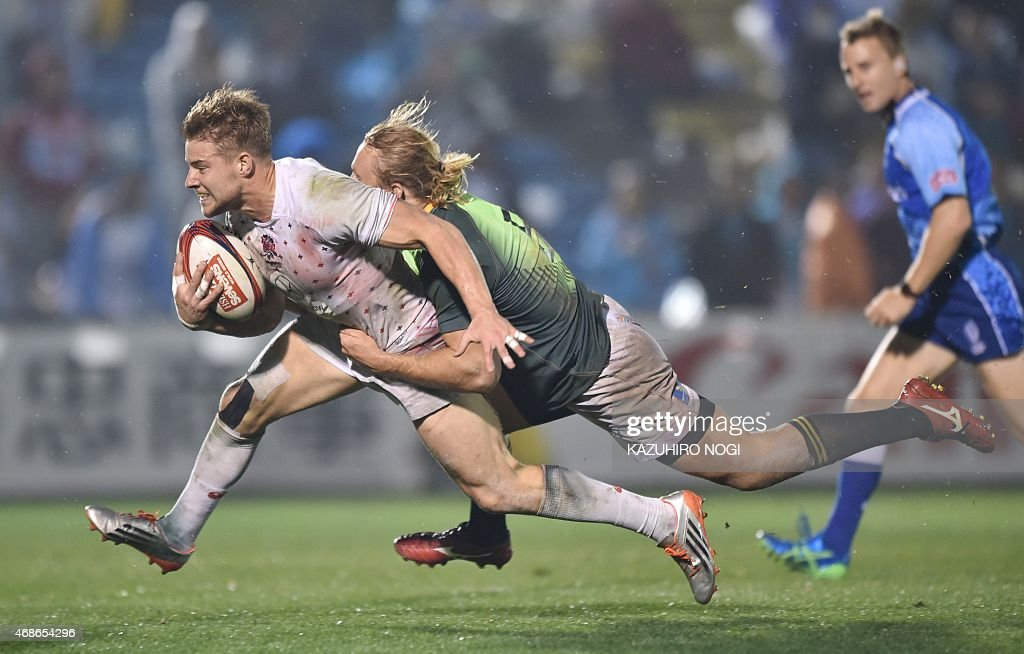 England's Tom Mitchell goes for a try as he is tackled by South Africa's Werner Kok during their final match at the Tokyo Rugby Sevens in Tokyo on...