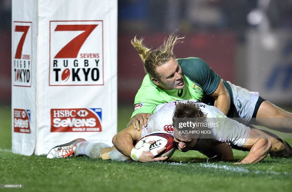 England's Tom Mitchell scores a try as he is tackled by South Africa's Werner Kok during their final match at the Tokyo Rugby Sevens in Tokyo on...