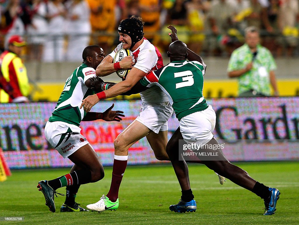 England's Tom Powell (C) is tackled by Kenya's Horace Otieno and Willy Ambaka during the cup final at the Westpac Stadium on day two of the fourth leg of the IRB Rugby Sevens World Series in Wellington on February 2, 2013. AFP PHOTO / Marty MELVILLE