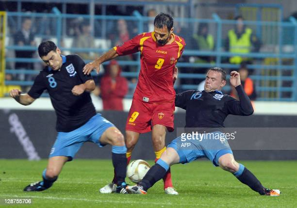 England's Wayne Rooney and Gareth Barry vies with Montenegro's Mirko Vucinic during the Euro 2012 group G qualifying football match Montenegro vs...