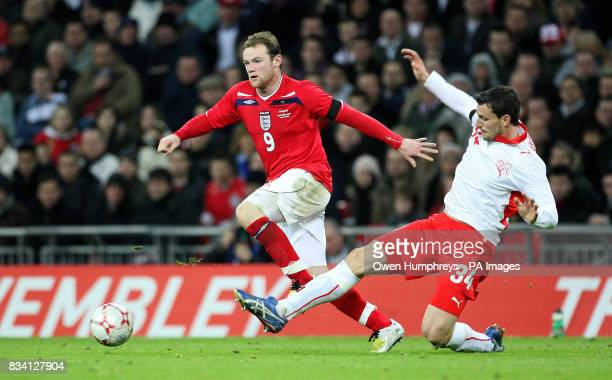 England's Wayne Rooney in action with Switzerland's Mario Eggimann during the International Friendly match at Wembley Stadium London