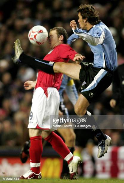 England's Wayne Rooney is tackled by Uruguay's Diego Godin during the friendly International match at Anfield Liverpool