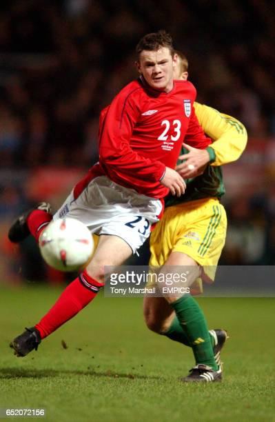 England's Wayne Rooney on his debut is held back by Australia's Craig Moore