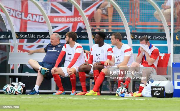 England's Wayne Rooney wipes the sweat off his face alongside teammates Adam Lallana Danny Welbeck and Jordan Henderson