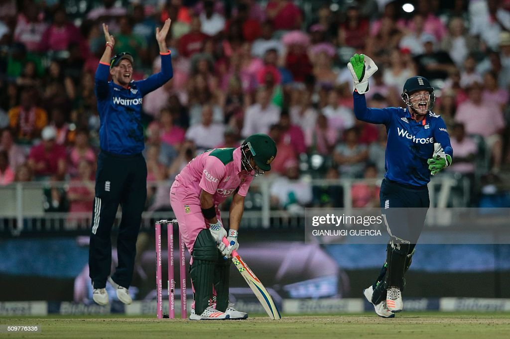 England's wicket keepers Jason Buttler (R) and fielder Joe Root (L) celebrates the dismissal of South African batsman JP Duminy (C) during the fourth One Day International match between England and South Africa at Wanderers on February 12, 2016 in Johannesburg. South African player are dressed in pink to raise awareness for breast cancer. / AFP / GIANLUIGI GUERCIA