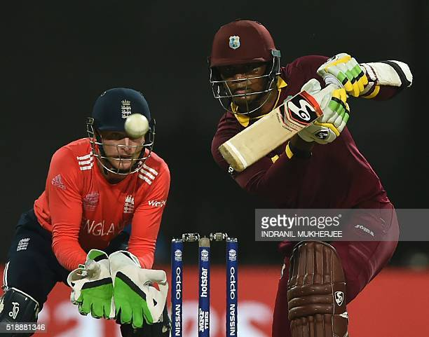 England's wicketkeeper Jos Butlerlooks on as West Indies's Marlon Samuels plays a shot during the World T20 cricket tournament final match between...