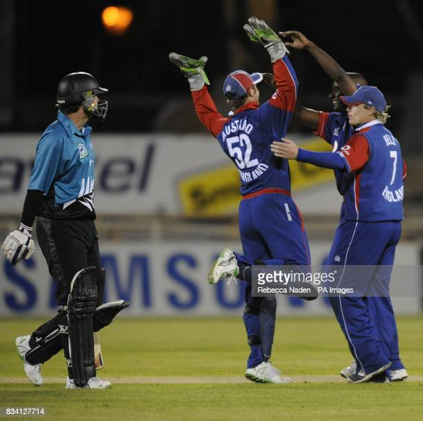 England's wicketkeeper Phil Mustard celebrates with Dimitri Mascarenhas after taking a wicket during the National Bank Twenty20 International match...