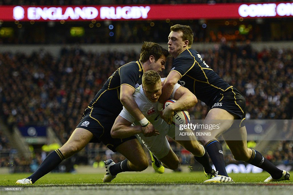 England's wing Chris Ashton (C) breaks through tackles from Scotland's full back Stuart Hogg (R) to score a try during the Six Nations international rugby union match between England and Scotland at Twickenham Stadium in south-west London on February 2, 2013. AFP PHOTO / ADRIAN DENNIS